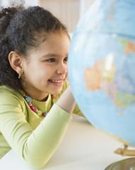 Hispanic girl looking at globe