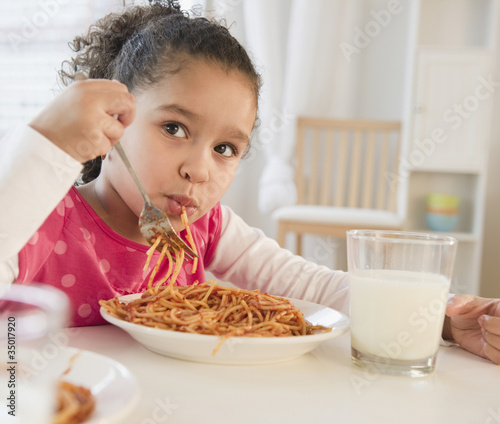 Hispanic girl eating spaghetti
