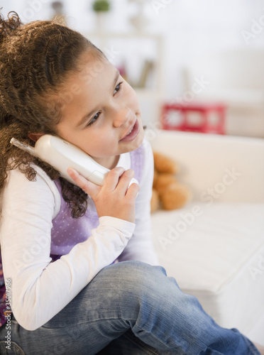 Hispanic girl talking on telephone