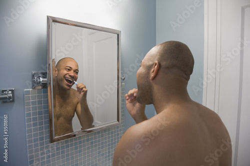 Mixed race man brushing teeth