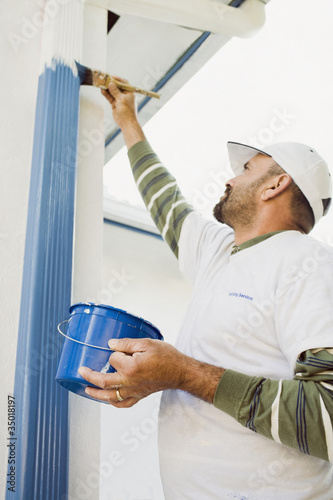 Latin man painting gutters