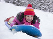 Laughing Japanese girl sledding