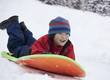 Laughing Japanese boy sledding