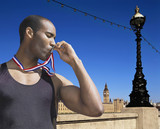 Black athlete kissing medal
