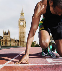 Black runner kneeling at starting block