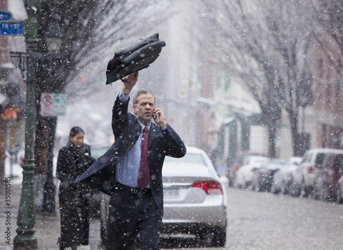Caucasian businessman hailing taxi in snow