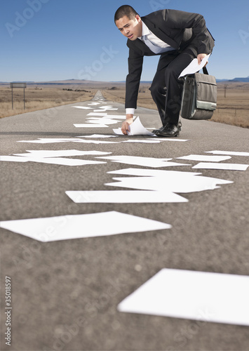 Asian businessman retrieving papers from roadway