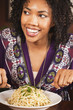African American woman eating bowl of pasta