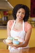 African American business owner holding dish of cupcakes in cafe