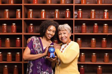 African American women holding prize-winning jar of sauce