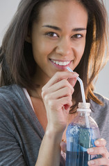 Mixed race woman drinking soda through straw