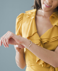 Mixed race woman putting on bracelet