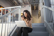 Ecuadorian businesswoman using laptop on staircase