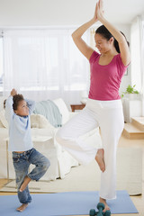 Mixed race mother and son practicing yoga