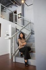 Ecuadorian businesswoman sitting on staircase with laptop