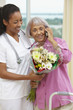 Nurse helping African American woman talking on cell phone