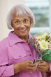 African American woman with bouquet text messaging on cell phone