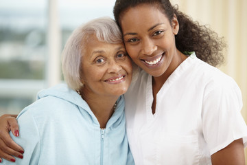 African American nurse hugging senior woman