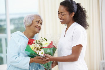 African American woman giving nurse bouquet of flowers