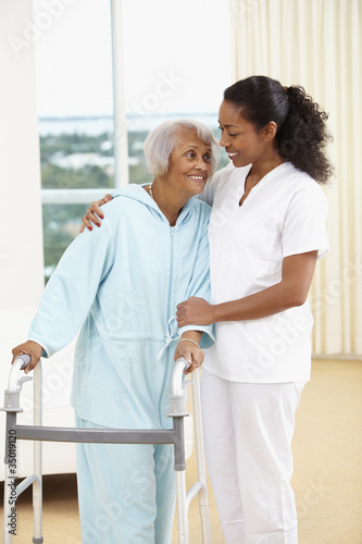 African American nurse helping senior woman with walker