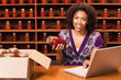 African American woman with laptop holding jar of sauce