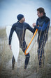 Men wearing wetsuits and carrying surfboards
