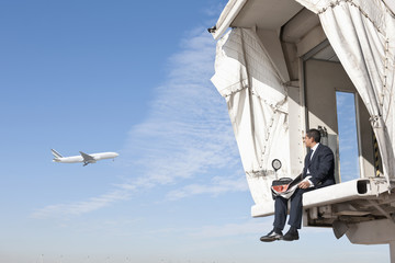 Hispanic businessman sitting on jetway