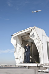 Hispanic businessman standing on jetway