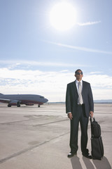Hispanic businessman standing on airport tarmac