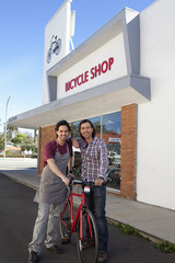 Bike shop owners standing outside shop with bicycle