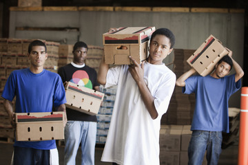 Men carrying cardboard boxes in warehouse
