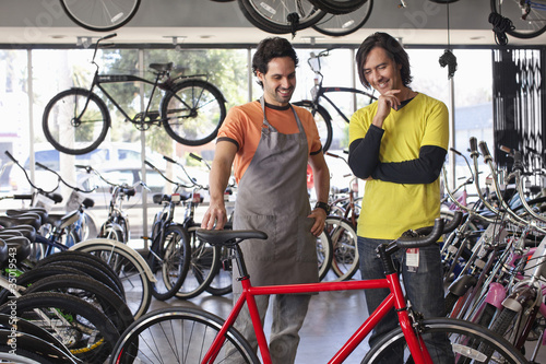 Bike shop owner helping customer choose bicycle