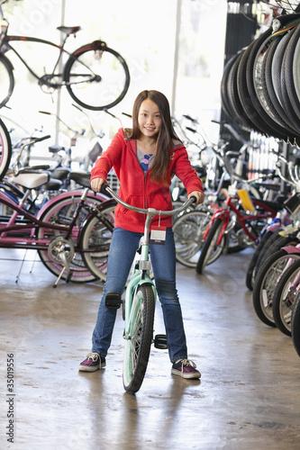 Mixed race girl choosing bicycle in shop