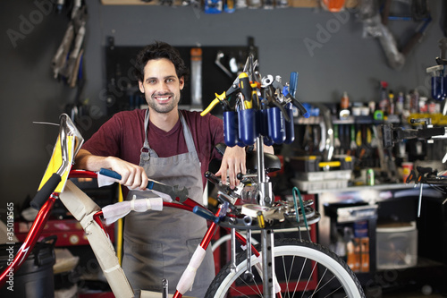 Hispanic man assembling bicycle in shop