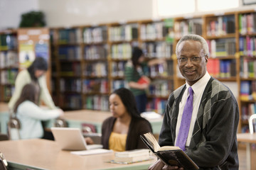 Black librarian reading book in school library