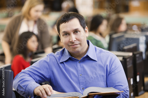 Mixed race man reading book in school library