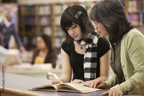 Filipino librarian helping student in school library