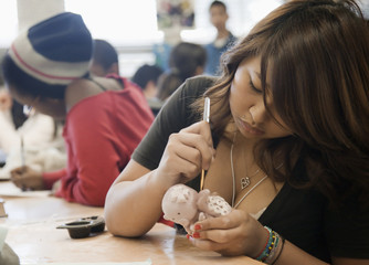 Student painting figurine in classroom