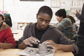 Student working with clay in classroom
