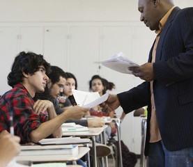 Teacher handing papers to students in classroom