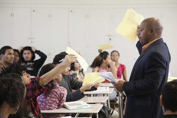 Teacher holding papers in classroom