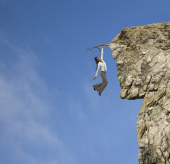 African American woman clinging to branch on cliff
