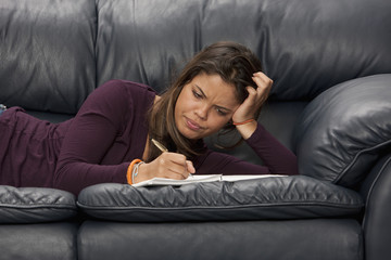 Mixed race woman doing homework on couch