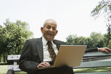 Senior Hispanic man with laptop in park