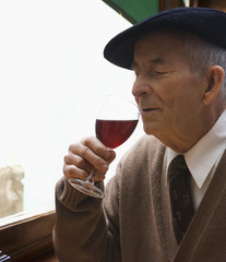 Senior Hispanic man drinking red wine