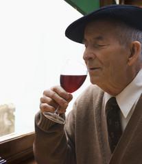 Senior Hispanic man drinking red wine