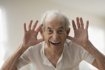 Senior Hispanic man making silly gesture