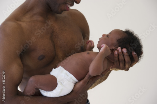 Black father holding newborn baby