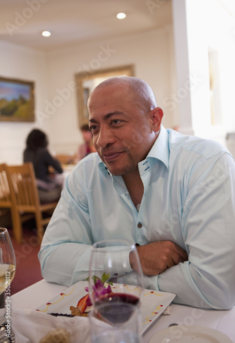 Mixed race man having dinner in restaurant
