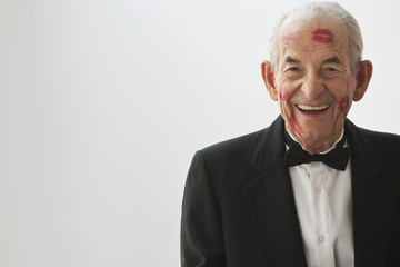 Smiling Hispanic man with lipstick kisses on his face